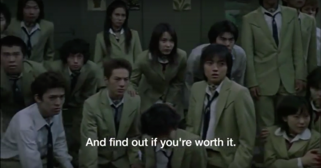 """Pictured here is a scene from the English sub of the Battle Royale film version, before things get messy. Several teenagers in school uniform are being told the premise of the Battle Royale game. The subtitle text, """"And find out if you're worth it,"""" appears at the bottom of the screen."""